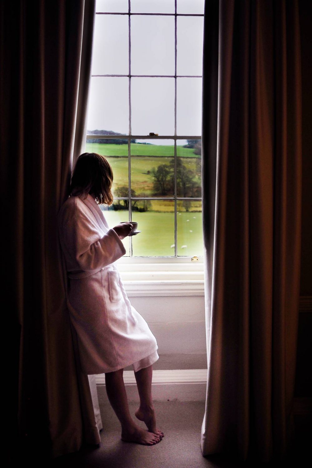 Sophie standing at the window with a cup of coffee overlooking the Welsh hills at Nanteos Mansion