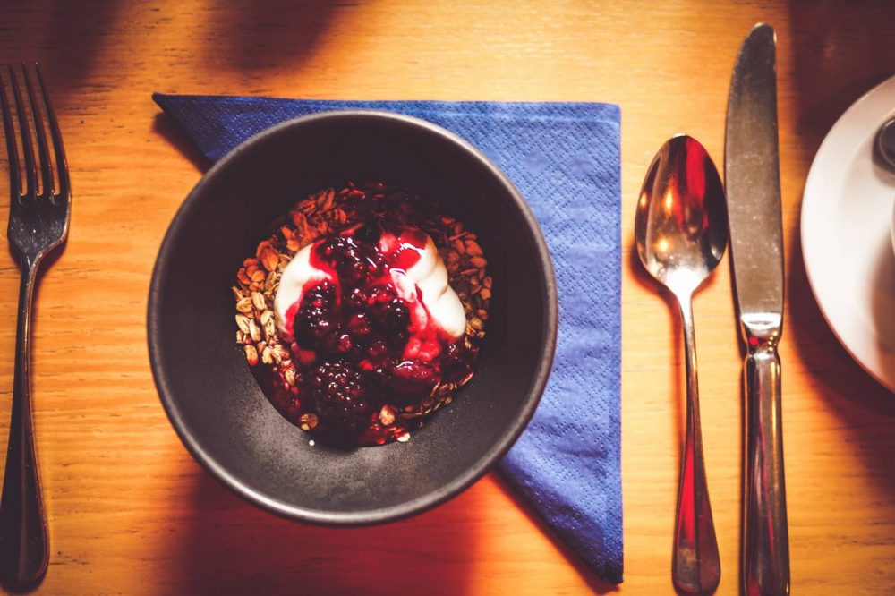 Bowl of granola, honey and fruit