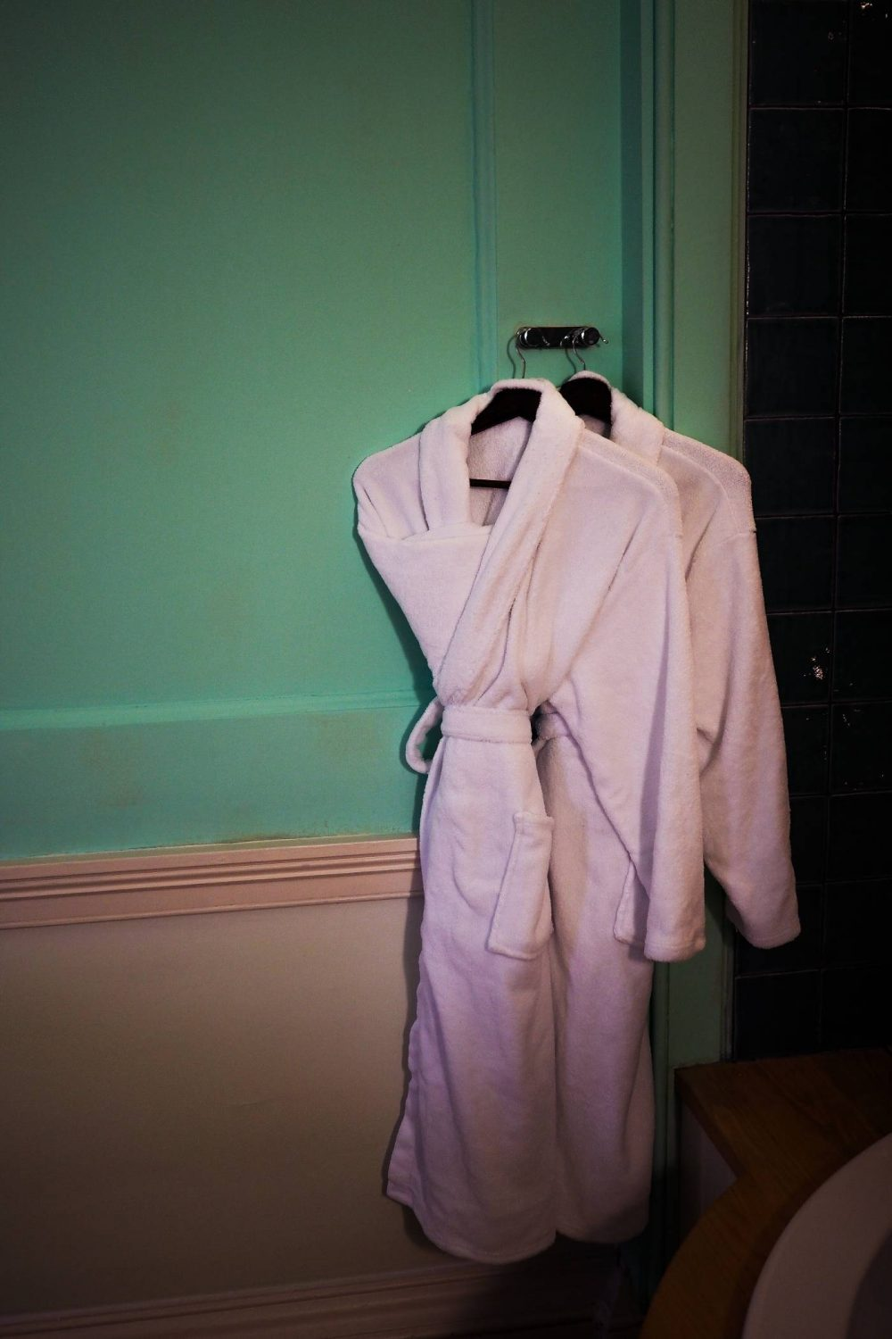 Two dressing gowns hanging on the wall