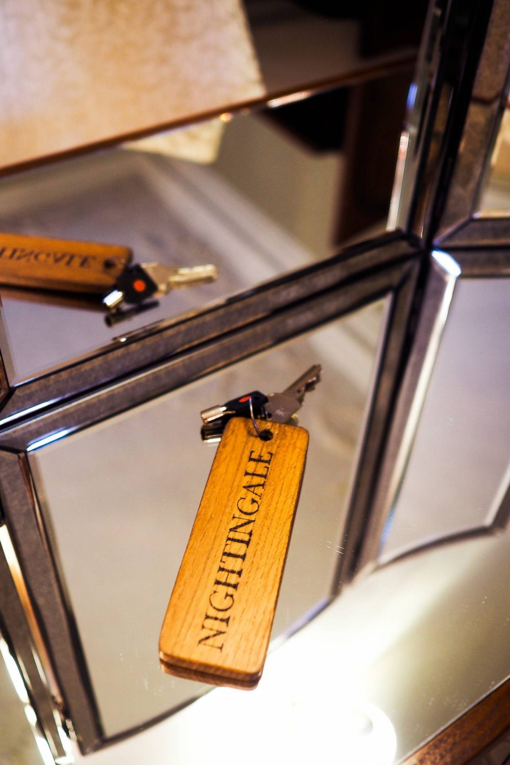 Wooden key tag that says 'Nightingale' on a mirrored dressing table