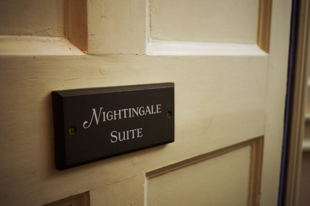 Slate sign reading 'Nightingsale Suite' on the door of the room at Nanteos Mansion