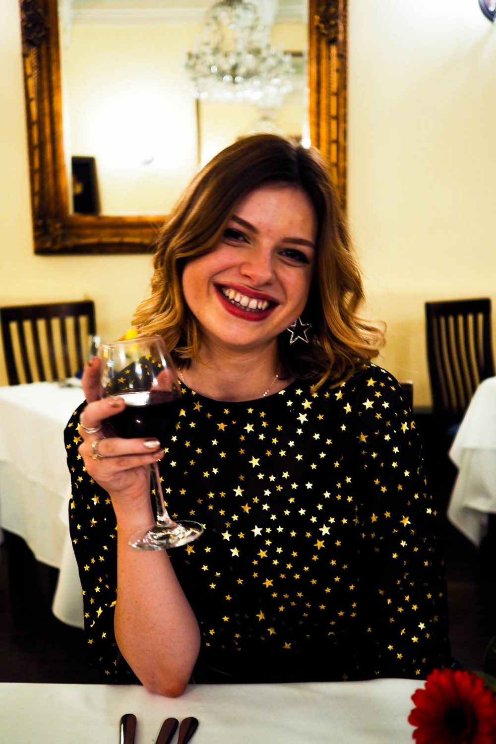 Sophie holding a glass of red wine in the Nightingale Restaurant at Nanteos Mansion