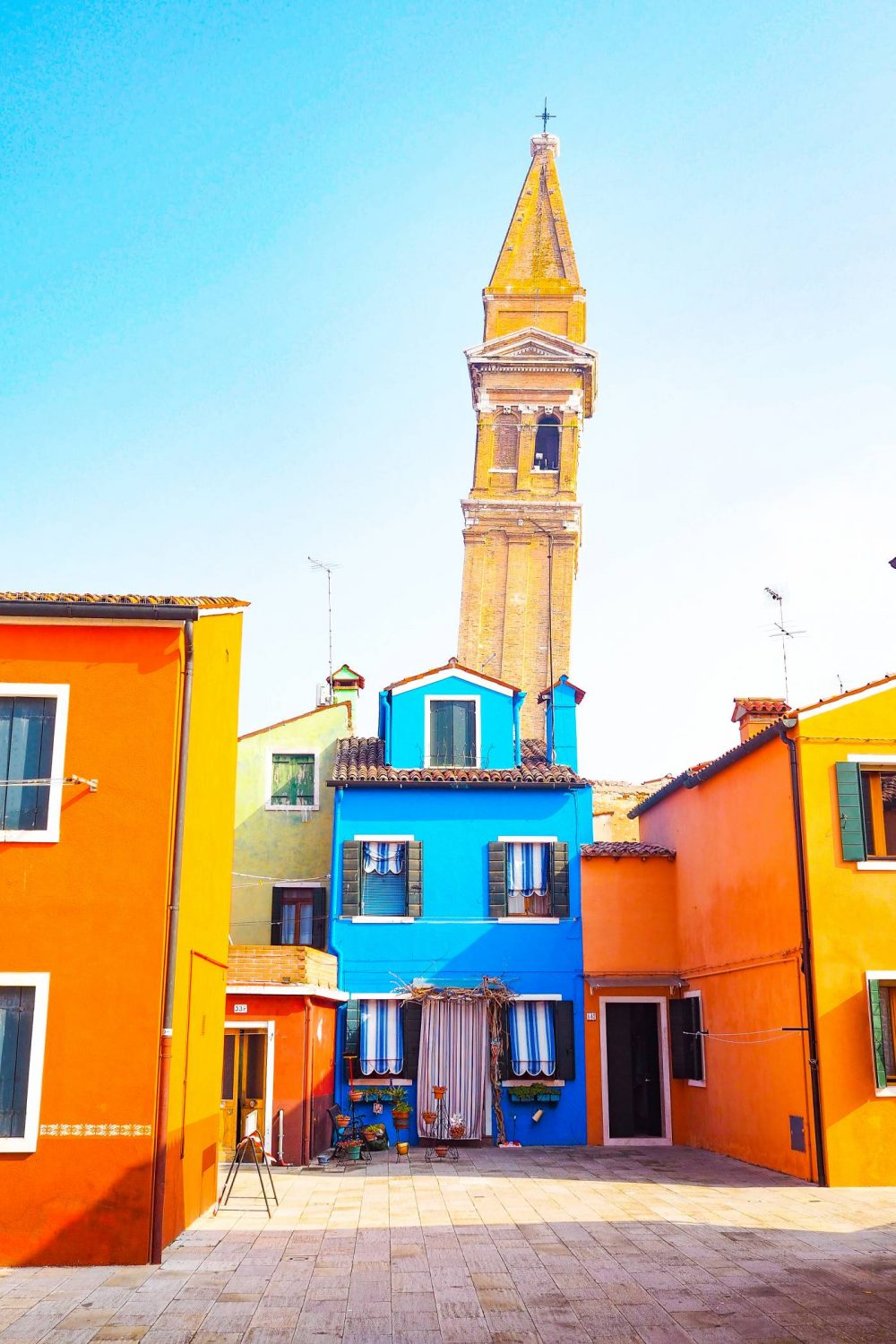 Burano Clock tower behind a bright blue house