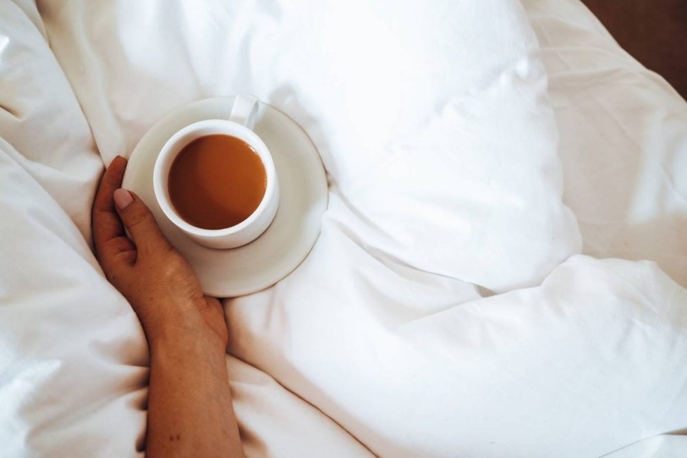 Cup of tea and saucer on top of white bed sheets