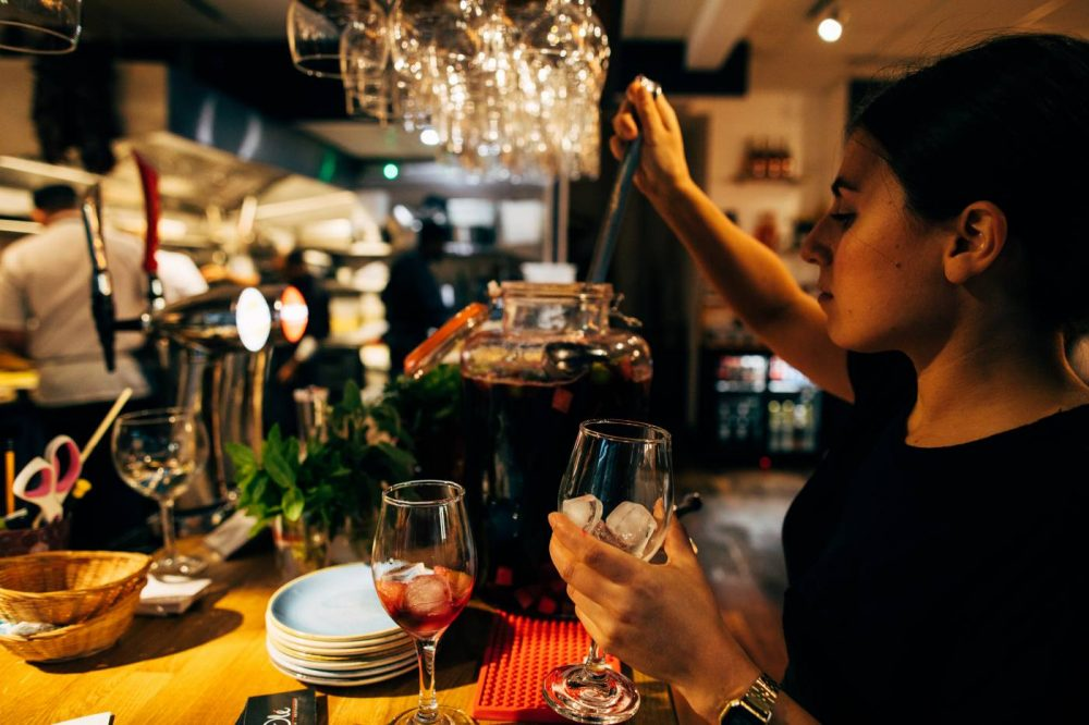 A waitress pouring sangria at Olé Tapas Bar