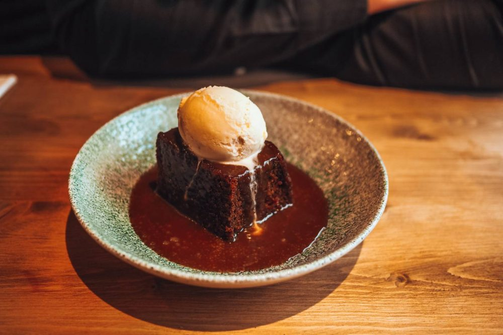 Sticky toffee pudding topped with vanilla ice cream at The Anchor, Aspley Guise
