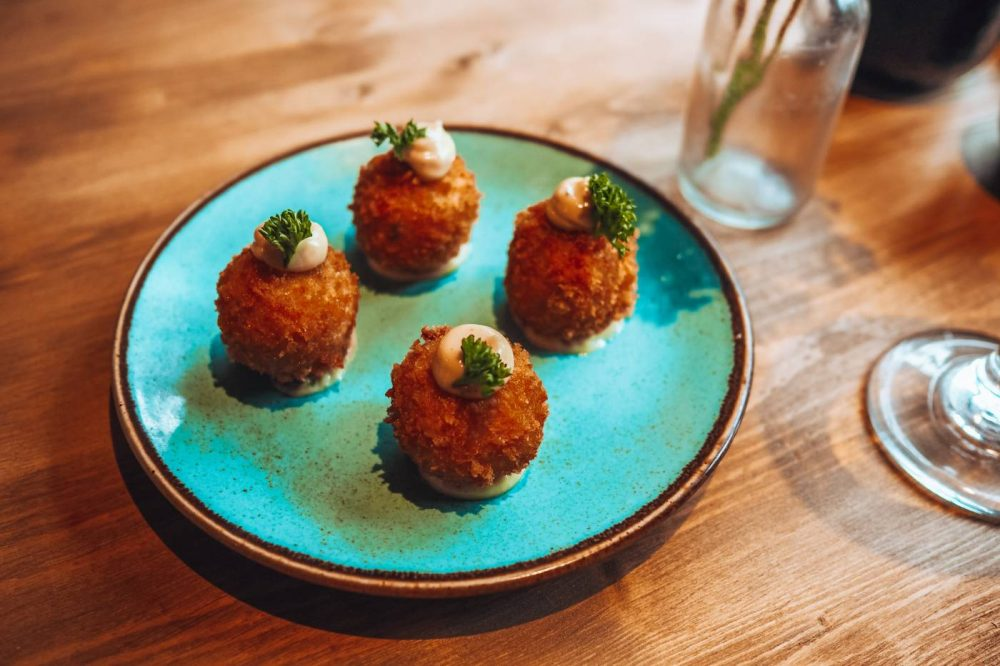 Cheese, chorizo and tarragon croquettes on a blue plate at The Anchor, Aspley Guise