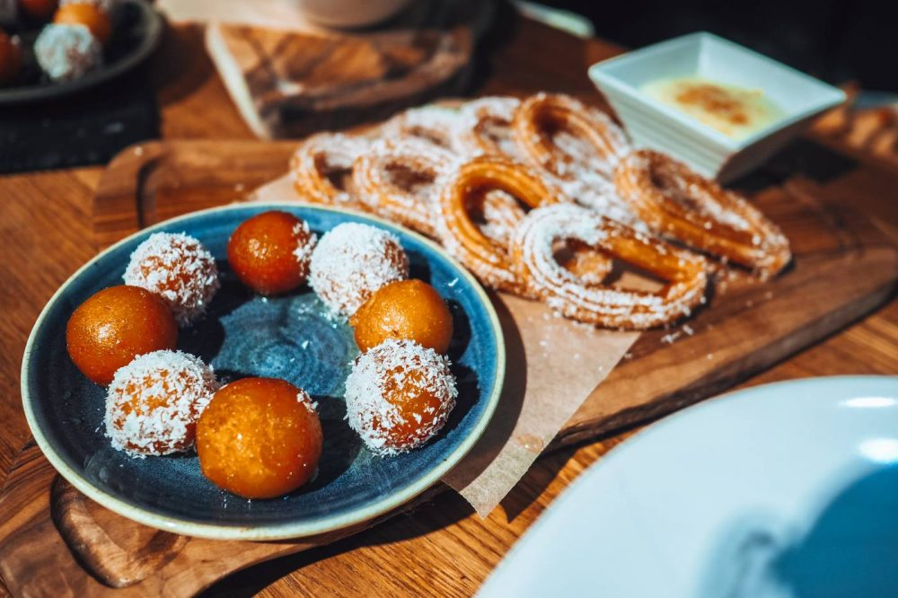 A board of gulab jamun, churros in coconut sugar and rice pudding