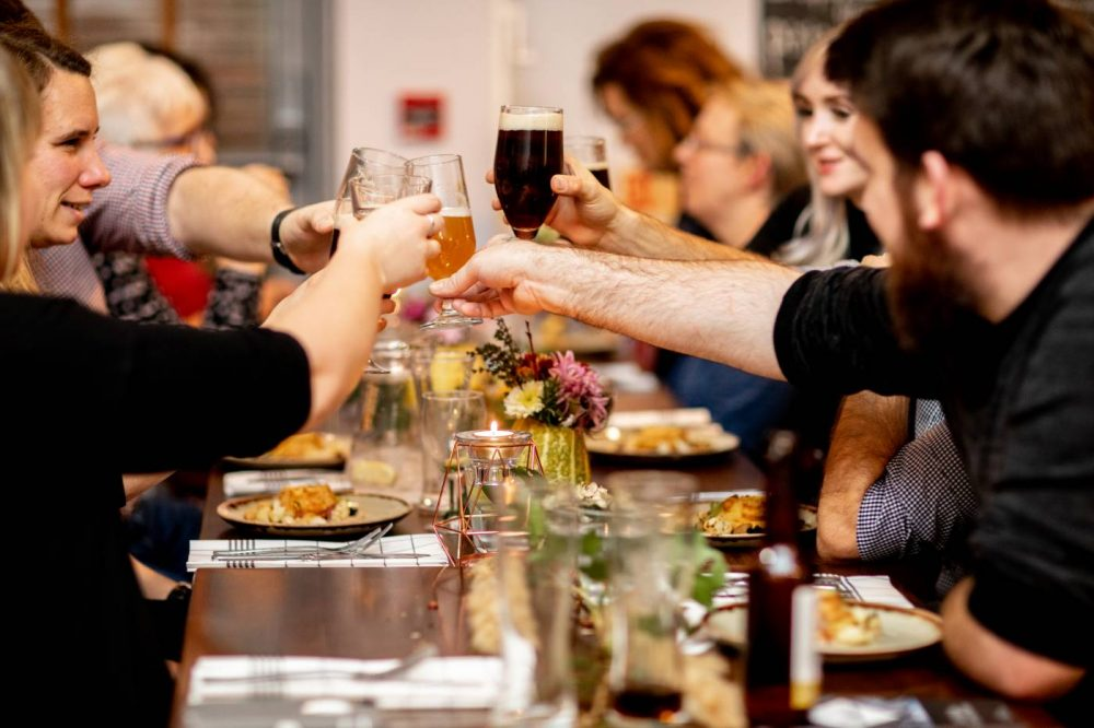 Guests doing cheers at Sophie's Supper Club at The Brasserie at MK College.