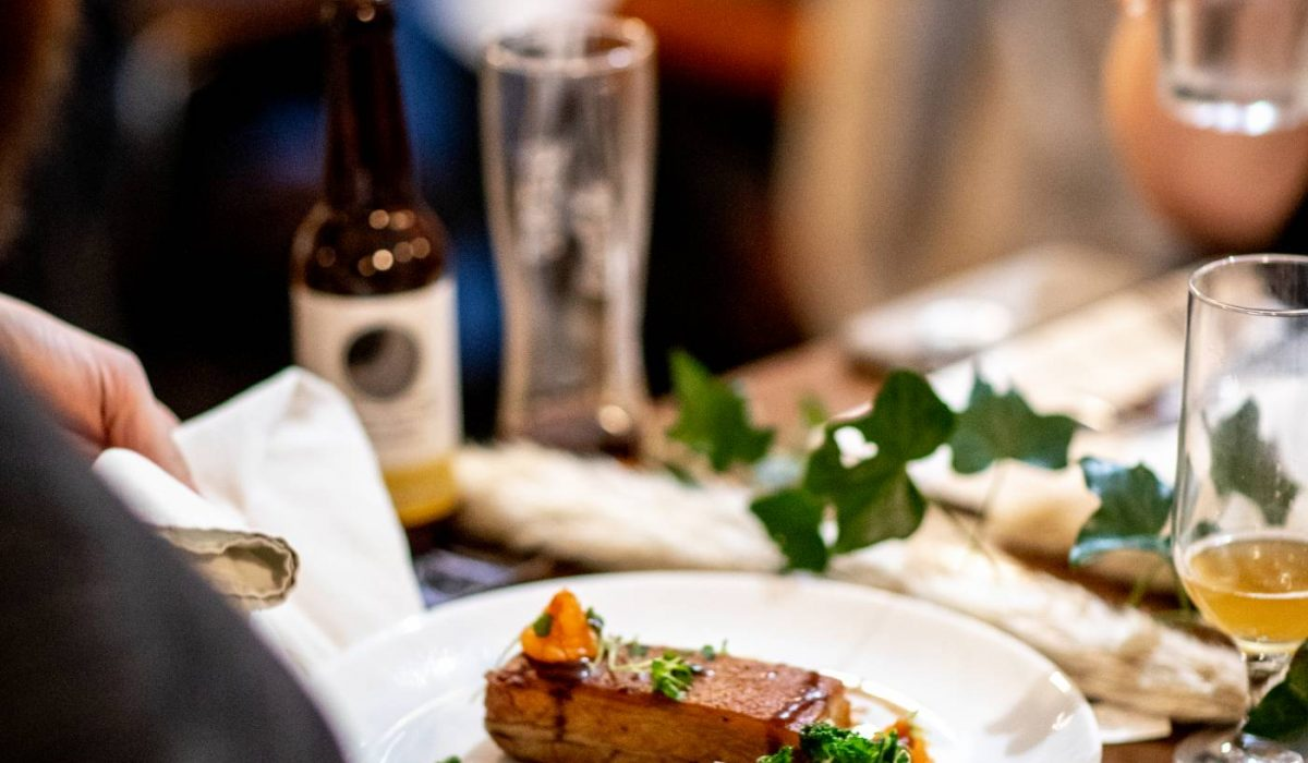 A photo of pork belly over someone's shoulder at The Brasserie