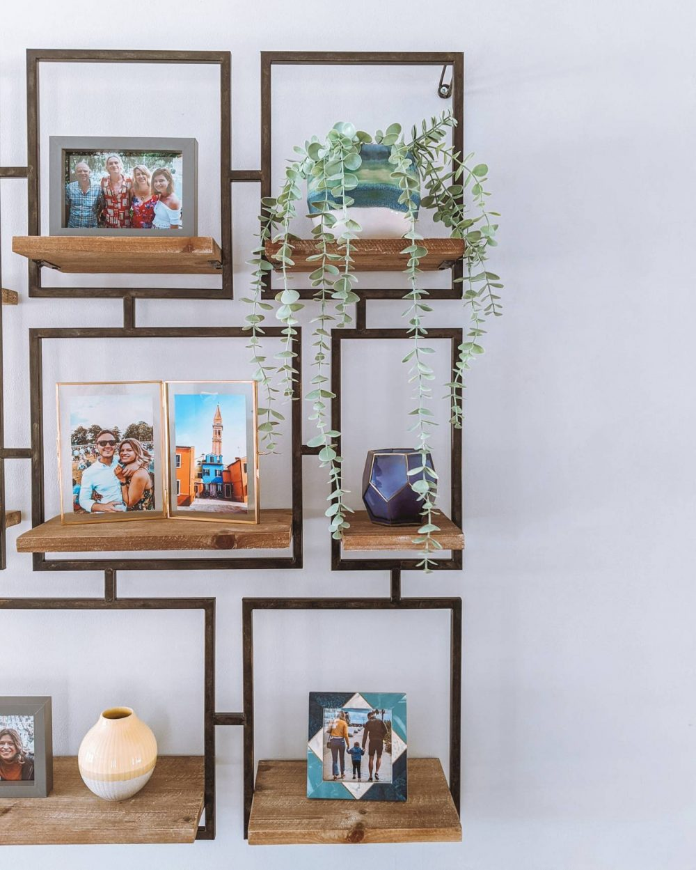 A steel shelf with photo frames and pots. It features a blue icelandic inspired pot by Andrew MacDermott Photography