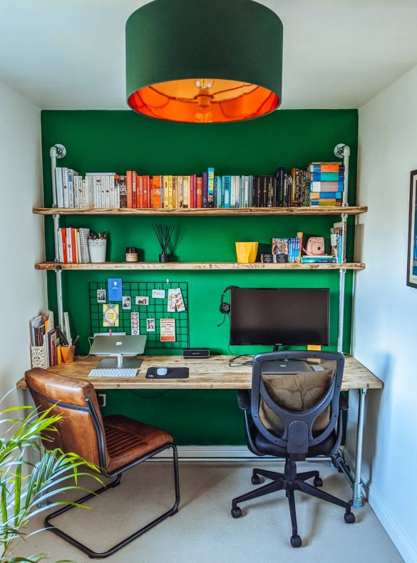 A custom wooden desk and shelving unit from Outhouse by Hand on a deep, forest green wall.