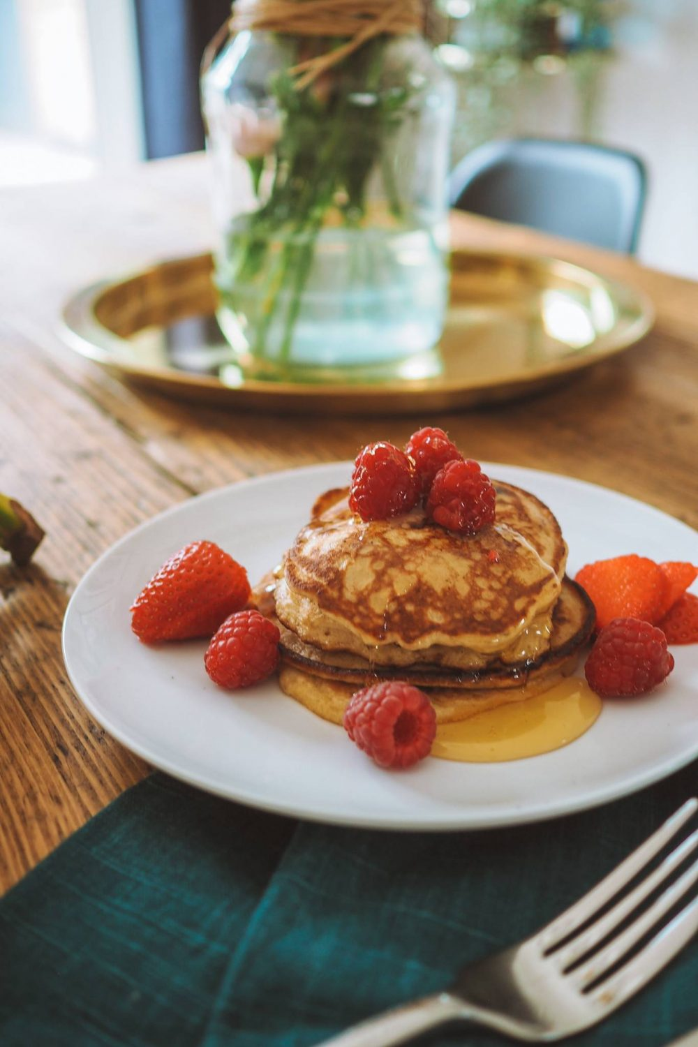 Banana pancakes topped with raspberries and honey