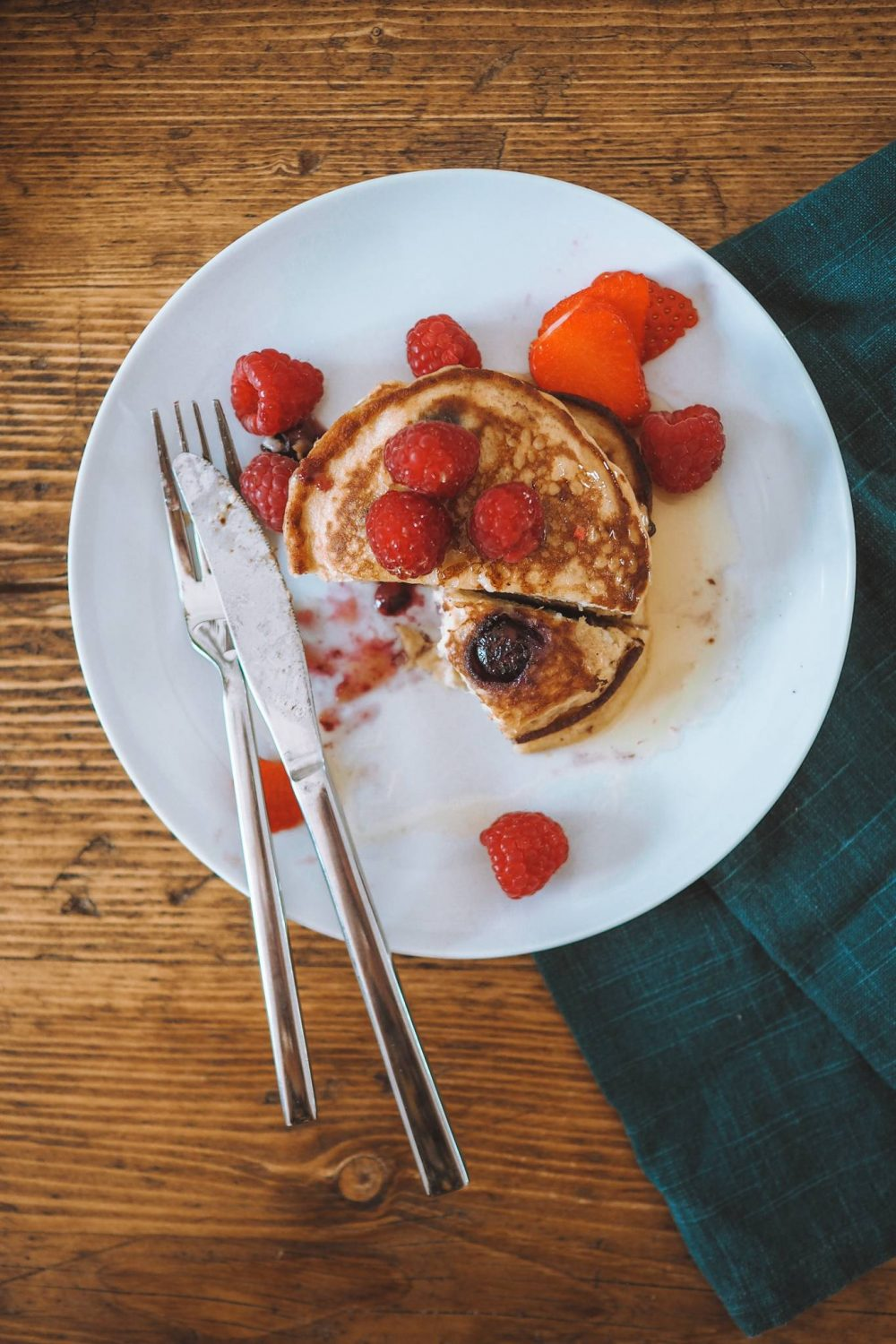 A plate of banana pancakes with raspberries topped with honey