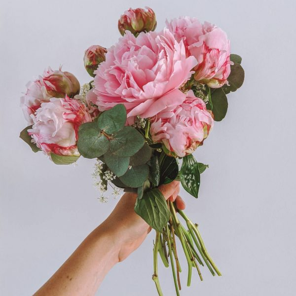 A bouquet of pink peonies held up against a white wall