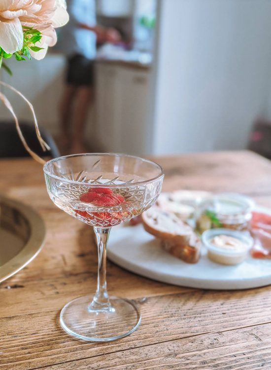 A photo of a crystal cut champagne saucer filled with champagne and raspberries