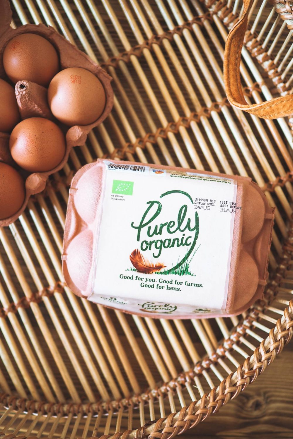 A flat lay image of a box of Purely Organic Eggs on a bamboo tray