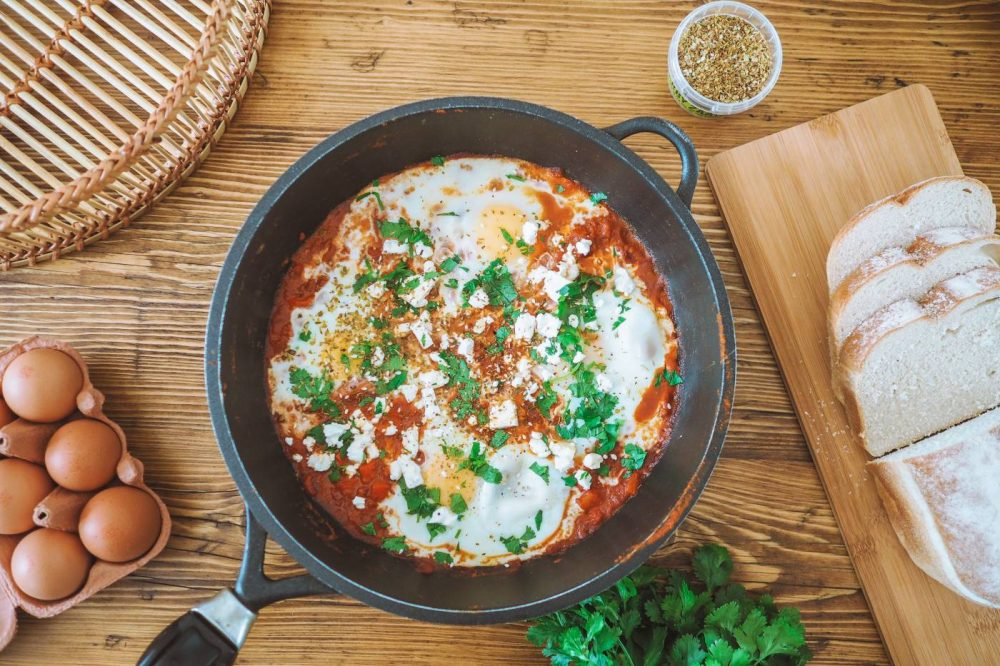 Shakshuka Recipe: A flatlay image of a pan of shakshuka on a wooden table.
