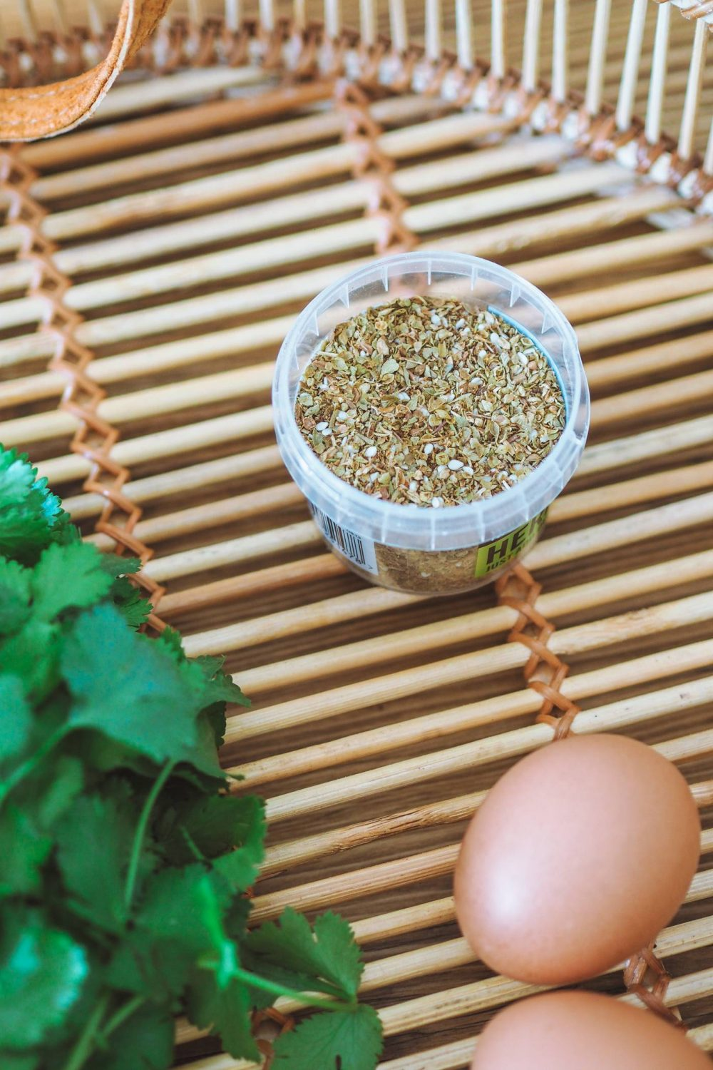 A pot of Za'atar, eggs and fresh coriander on a bamboo tray