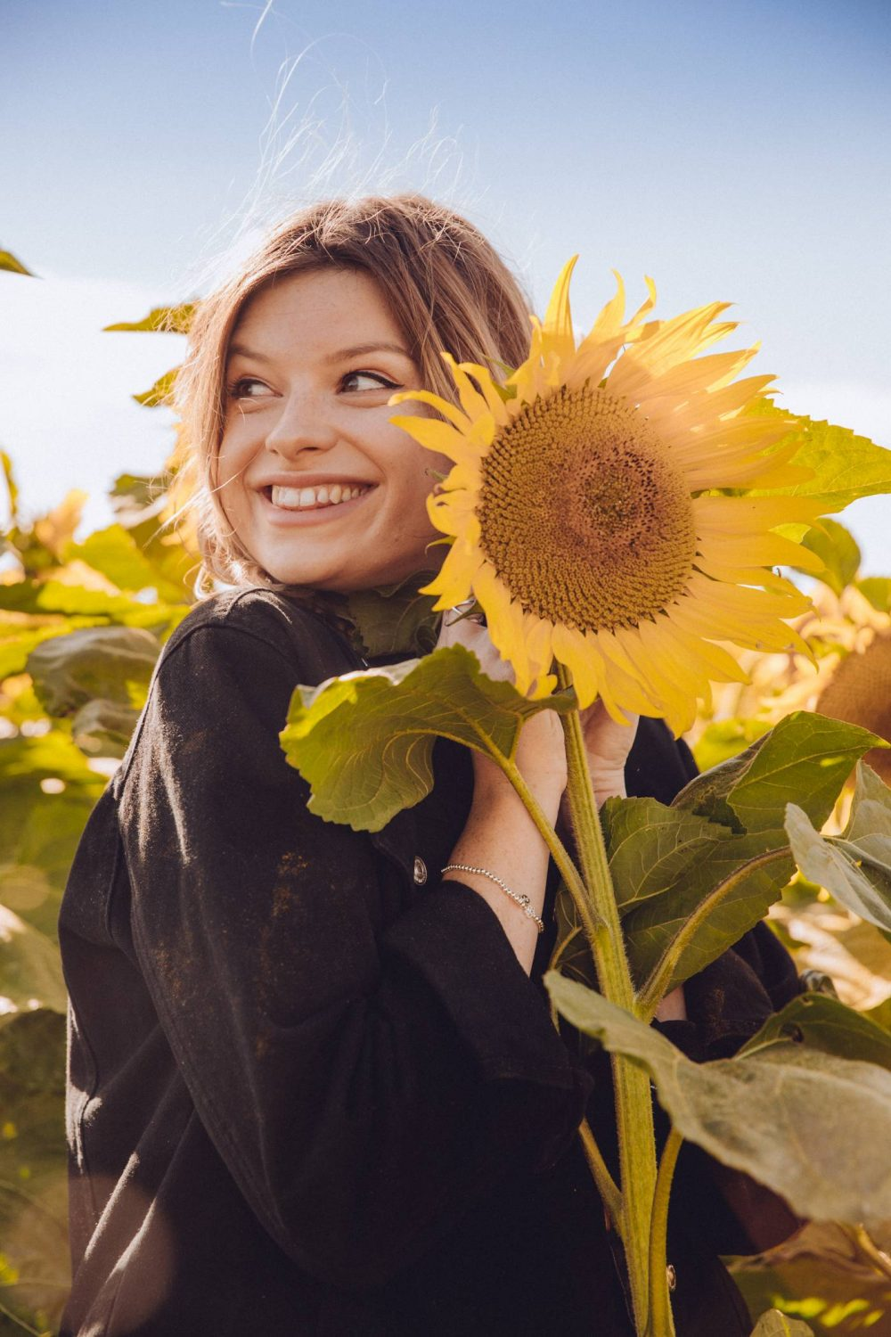 Sophie etc smiling with a giant sunflower at the Patch MK