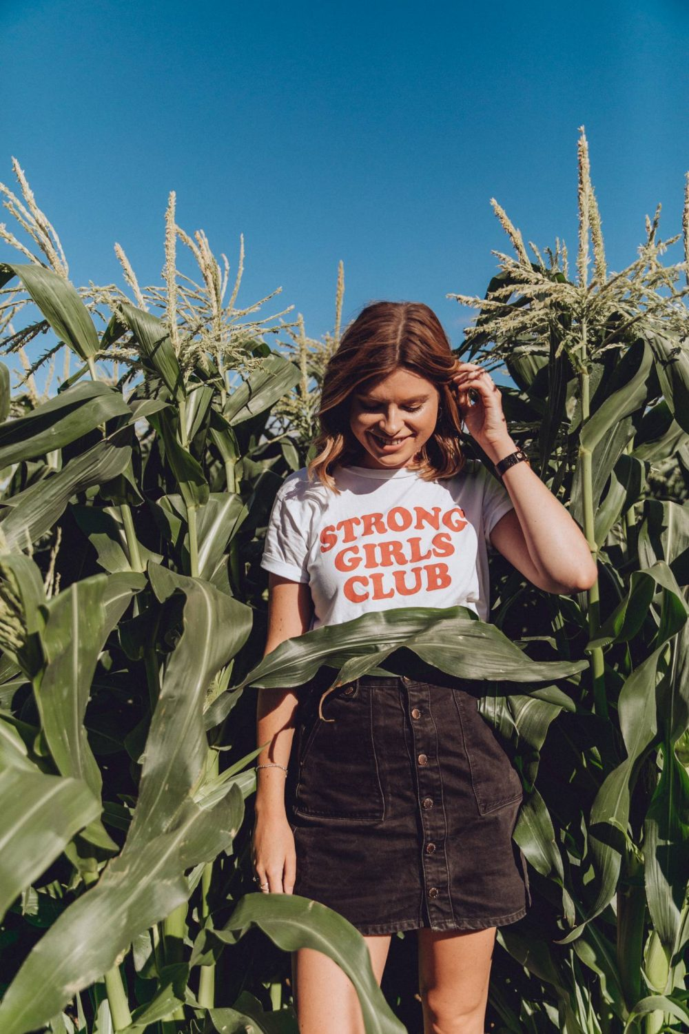Sophie wearing a white t-shirt with 'Strong Girls Club' in red lettering on the front, standing in a field of corn at The Patch MK.